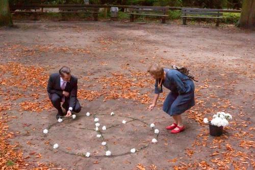 Dr. Felix Schwenke und Christa Fuehrer-Roessmann legen ein Peace-Symbol aus Nelken